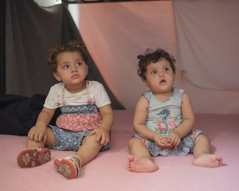 Aziza, two, and her sister Madjida, one, sit on their bunkbed at PIKPA, a refuge opened in January 2016 by the Leros Solidarity Network as a shelter for refugee families and unaccompanied minors. The sisters have different mothers but their father Hasan and Madjida's mother Mariam take care of them both as Aziza's mother is still in Syria with another one of her children.