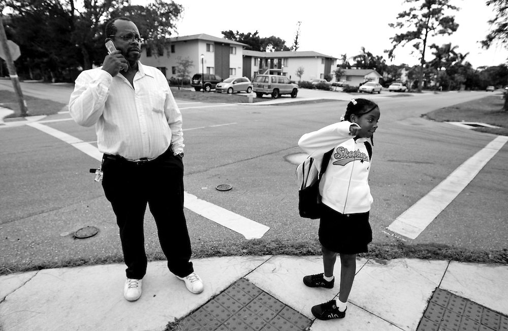 "Douglas Bolden waits with his daughter Selena, 8, right, for the school bus, which was running late. ""Not today, this can't happen today,"" Bolden said as he called the school about the tardy bus. Bolden, who has no car and can not obtain a license until more than $4,000 of motor vehicle violations are paid for in New Jersey, was going to be attending a career fair that day and didn't want to be late. Greg Kahn/Staff"