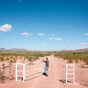 "A man opens a gate in the Mexico/US Border near Agua Perieta, Mexico and Douglas, Arizona. Hundreds of undocumented immigrants pass across the desert here, and dozens die every year from dehydration and exposure. The man, part of a group called ""Agua Por Vida"" leaves water for those attempting to cross. They do not encourage people to cross the nearly 2,000 mile border but do not believe people should die needlessly."