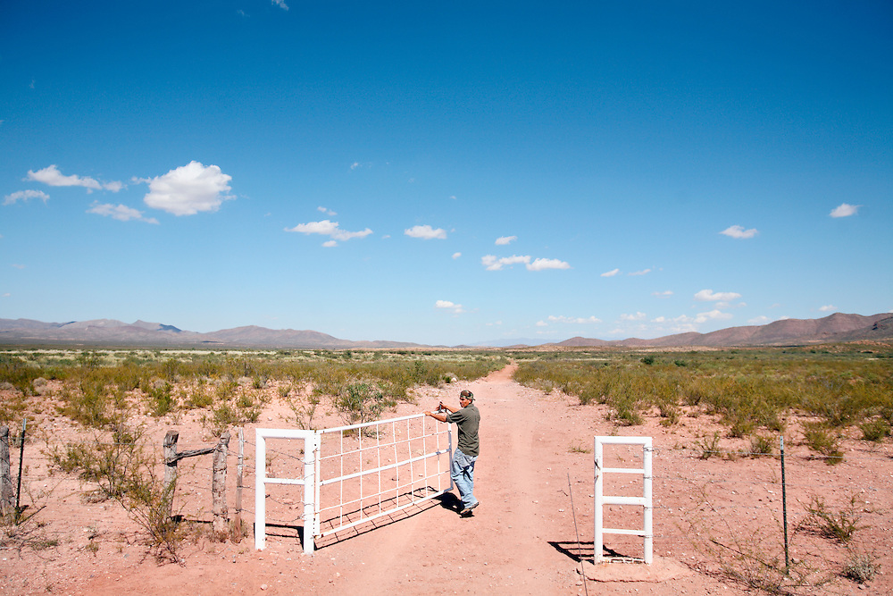 """A man opens a gate in the Mexico/US Border near Agua Perieta, Mexico and Douglas, Arizona. Hundreds of undocumented immigrants pass across the desert here, and dozens die every year from dehydration and exposure. The man, part of a group called """"Agua Por Vida"""" leaves water for those attempting to cross. They do not encourage people to cross the nearly 2,000 mile border but do not believe people should die needlessly."""