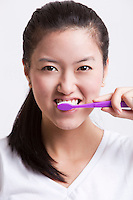 Portrait of young woman brushing her teeth against white background