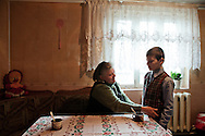 Alexandro (aged 10), with his grandmother Nina (aged 60) at their home. Nina, takes care alone of her two grandchildren, Alexandro and Gabriela (13). Both parents of the children are living abroad: The mother works in Italy and the father in France.