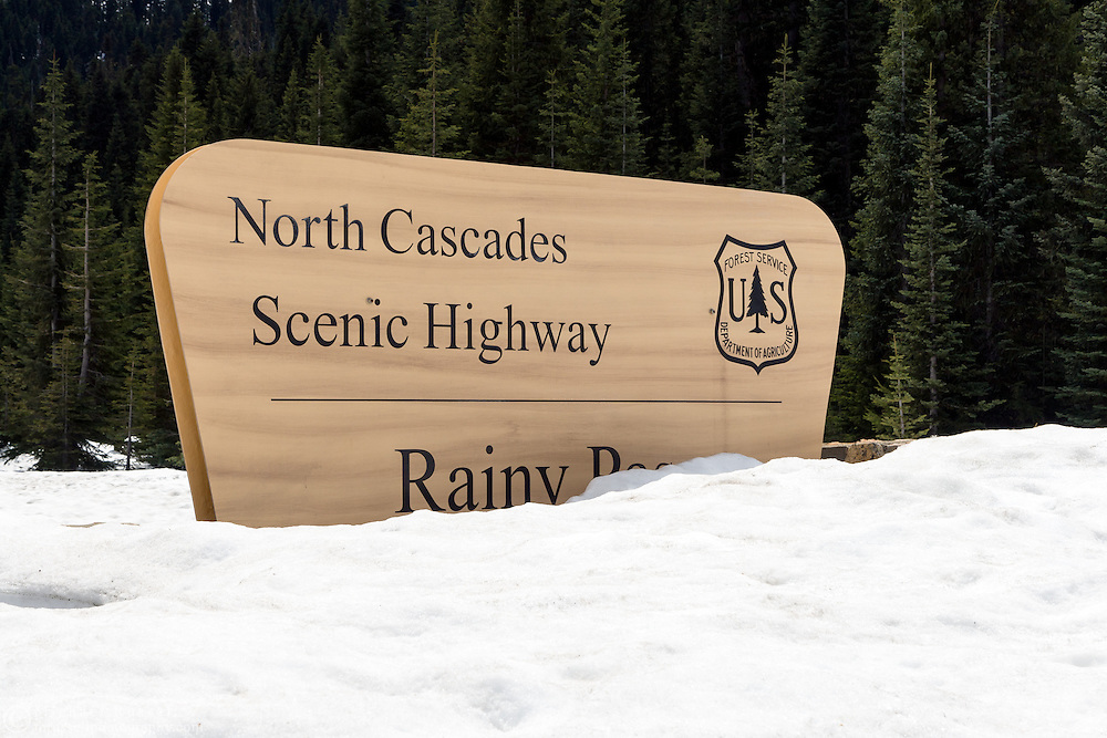 A sign at Rainy Pass in a snowbank along the North Cascades Scenic Highway in Washington State, USA.