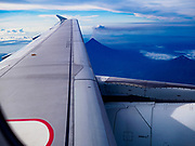 01 FEBRUARY 2018 - LEGAZPI, ALBAY, PHILIPPINES:  Philippine Express Airlines flight 2922, enroute Manila, an Airbus A320, flies past the Mayon volcano (lower center, below wing) after departing Legazpi. The Mayon volcano started erupting in the middle of January. The airspace around the volcano has been closed off and on for more than week. The airport is about 13 kilometers from the volcano and the ash clouds from Mayon pose a threat to aircraft engines. More than 80,000 people have been evacuated from their homes around the volcano.    PHOTO BY JACK KURTZ