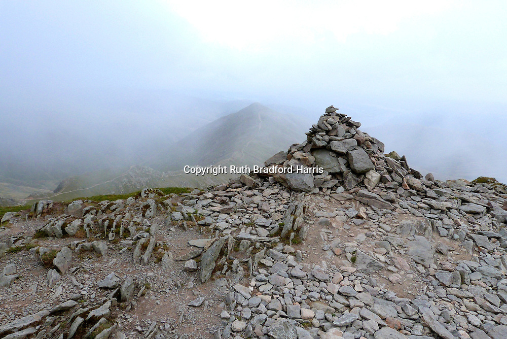View from the cairn marking the true summit of Helvellyn (at 950m) towards Catstye Cam, veiled in low cloud. Note the concave shape of the cairn mirrors that of Catstye Cam. I wonder if that's deliberate?<br />