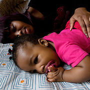 London, UK, December 19th 2001. .Teenage Parents Service at the Stockwell YMCA charity in Lambeth, South London..Sarah, 18 years old from Ghana, with her daughter Soraya, 7 months old. When she got pregnant she left the family and found accommodation at the YMCA Teenage Parents Service through the Local Council where she used to live.