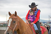 Woman and little girl riding on the back of a horse.
