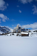 A snow covered wooden barn at the Alta Badia ski resort with Sassongher Mountain in the background.  Covara, The Dolomites, South Tyrol, Italy
