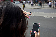 A woman checks messages on her mobile phone before crossing the road in Trafalgar Square, on 13th August 2018, in London, England.