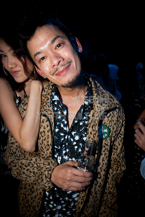 ASIAN GIRL DRAPED OVER ASIAN MALE WITH COOL BEARD IN BANGKOK NIGHTCLUB