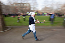 © Licensed to London News Pictures. 21/02/2012. LONDON, UK. Liberal Democrat MP Martin Horwood attempts to toss a pancake as he takes part in a pancake race outside the Houses of Parliament today (21/02/12). Lords, Members of Parliament and political journalists today took part in the 2012 'Rehab Parliamentary Pancake Race' in aid of disability charity Rehab. The parliamentary team took the trophy after an extra lap was run due to widespread cheating. Photo credit: Matt Cetti-Roberts/LNP
