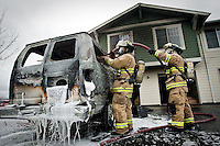 JEROME A. POLLOS/Press..Coeur d'Alene firefighters saturate the inside of a van full of carpet Friday that caught on fire and caused minor damage to the exterior of an apartment complex near Lake City High School. There were no injuries in the fire that completely destroyed the van and the cause is still under investigation.