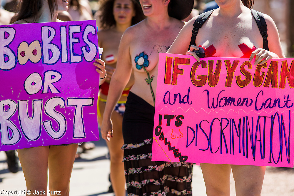 26 MARCH 2012 - PHOENIX, AZ:   Topless women and men march through Phoenix Sunday. About 40 people marched through central Phoenix Sunday to call for a constitutional amendment to give women the same right to go shirtless in public that men have. The Phoenix demonstration was a part of a national Topless Day of Protest. Phoenix prohibits women from going topless in public so protesters, women and men, covered their nipples and areolas with tape. The men did it to show solidarity with the women marchers.  PHOTO BY JACK KURTZ
