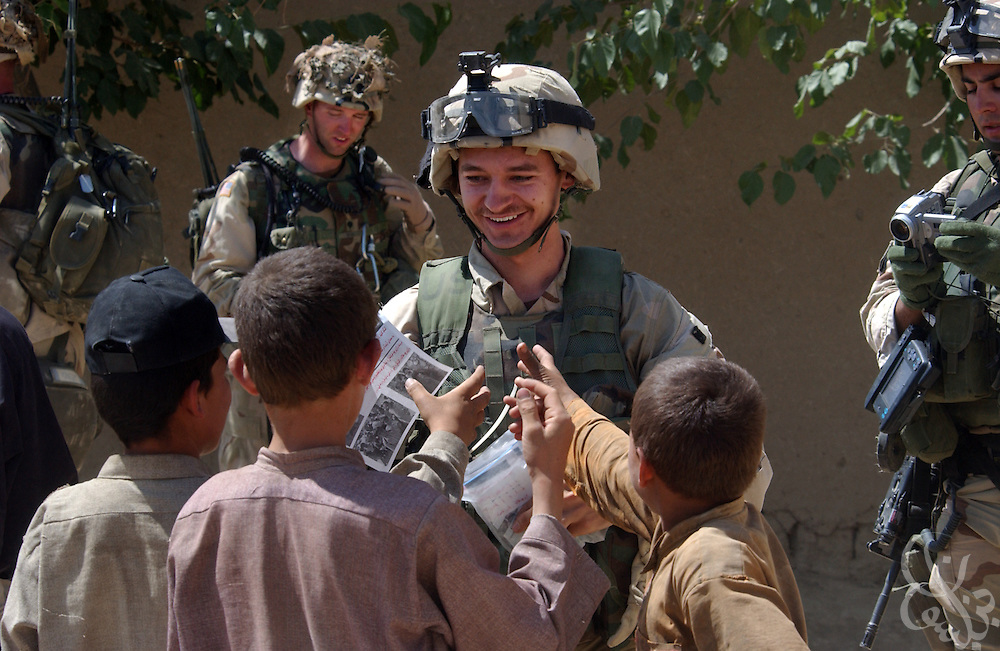 "U.S. Army psychological operations soldier Spc. Bobby hands out Army printed Dari language pamphlets during a ""sensitive site exploitation"" mission or SSE July 16, 2002 in village of Hesarak, eastern Afghanistan. The army raided the village to conduct a follow-up search for possible Al-Qaida or Taliban intelligence materials and to provide humanitarian aid. The raid was a follow-up to a similar raid there four days ago that yielded two detainees and undisclosed intelligence materials."