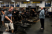 Defensive coordinator Mike Copeland works with players in the weight room at Stephenville High School in Stephenville, Texas on November 5, 2013. (Cooper Neill / for The New York Times)