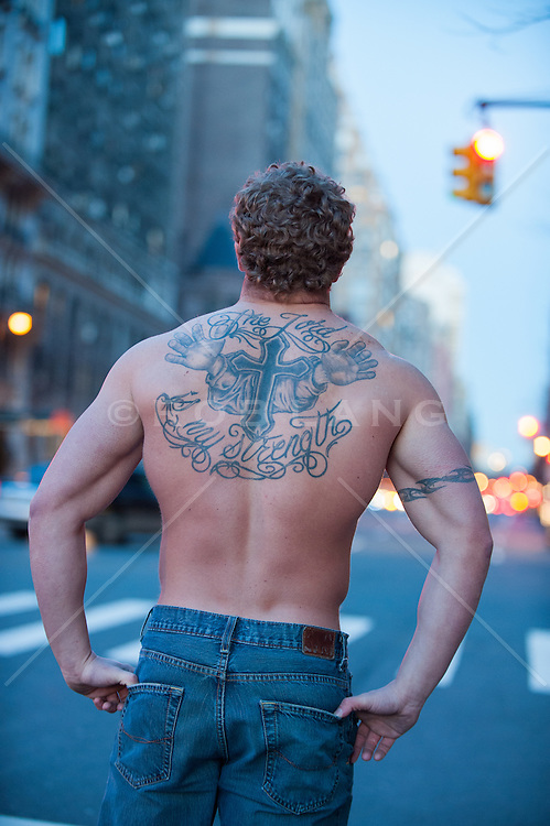 muscular man with tattoos on his back and arm in New York City