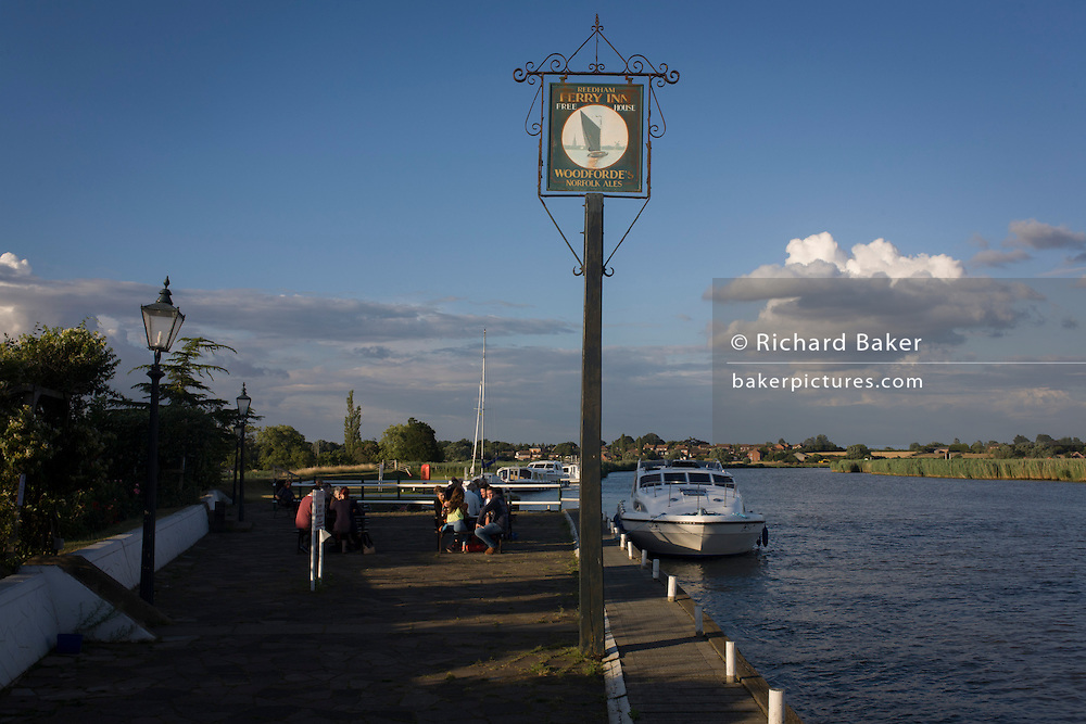 Riverside Ferry Inn sign and boating on the River Yare at Reedham on the Norfolk Broads.