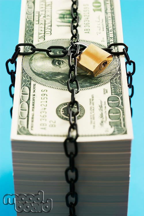 Stack of Dollars secured by padlock and chain