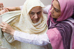 Young female carer helping an older woman put on her sari,