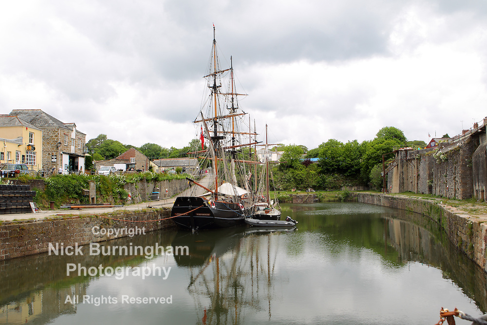 Charlestown Harbour, Charlestown, Cornwall, UK. 14th June, 2015. Two tall ships moored at Charlestown on a cloudy day. A number of popular 18th century television productions are filmed at the harbour and make use of the ships.