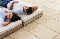Couple relaxing on sun beds on terrace elevated view