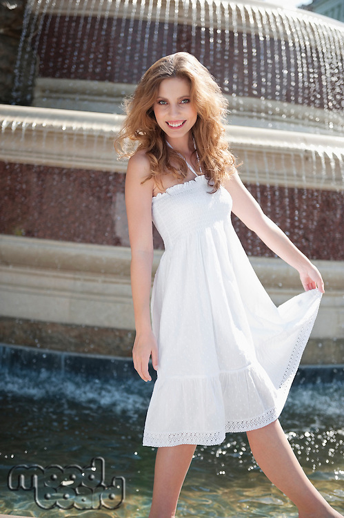 Portrait of happy young woman in white halter neck dress standing by water fountain