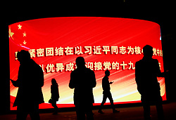 epa06267140 People walk past a large electronic billboard showing propaganda for the coming 19th National Congress with the words 'Unite closely with comrade Xi Jinping as the core of the Communist Party, welcome with good results the successful opening of the 19th National Congress' outside a shopping complex in Beijing, China, 15 October 2017. The Communist Party of China (CPC) is making preparations for the five-yearly 19th National Congress scheduled to begin on 18 October. During the Congress, members will elect a new Central Committee, including a new 24-member Politburo and a new seven-member Standing Committee.  EPA-EFE/HOW HWEE YOUNG