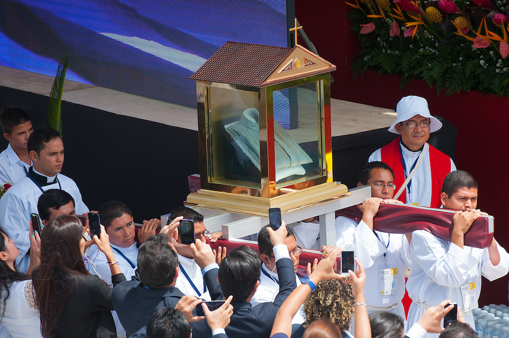 Salvadoran Catholic priests carry a relic - The blood stained shirt - of martyred Archbishop Oscar Romero .  The Archbishop was slain at the alter of his Church of the Divine Providence by a right wing gunman in 1980. Oscar Arnulfo Romero y Galdamez became the fourth Archbishop of San Salvador, succeeding Luis Chavez, and spoke out against poverty, social injustice, assassinations and torture. Romero was assassinated while offering Mass on March 24, 1980.