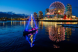Canada, British Columbia, Vancouver.  02 July, 2017. Lighted canoe and the geodesic dome of Science World at the east end of False Creek at dusk.