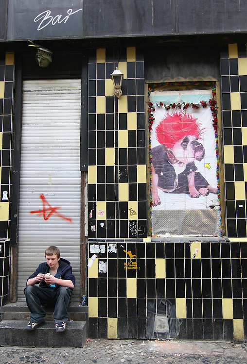 Deutschland - BERLIN - 1. Mai 2006 -  GERMANY - Party on MAY 1 in Kreuzberg; HERE: young man eating a Doener Kebab in Oranienstrasse;MyFEST Kreuzberg - Oranienstraße; Junger Mann isst ein Döner vor geschlossener Bar; Wandbild , Bulldogge mit Perücke.(das Fest wurde organisiert vom Kotti e.V.) .copyright > jungeblodt.com