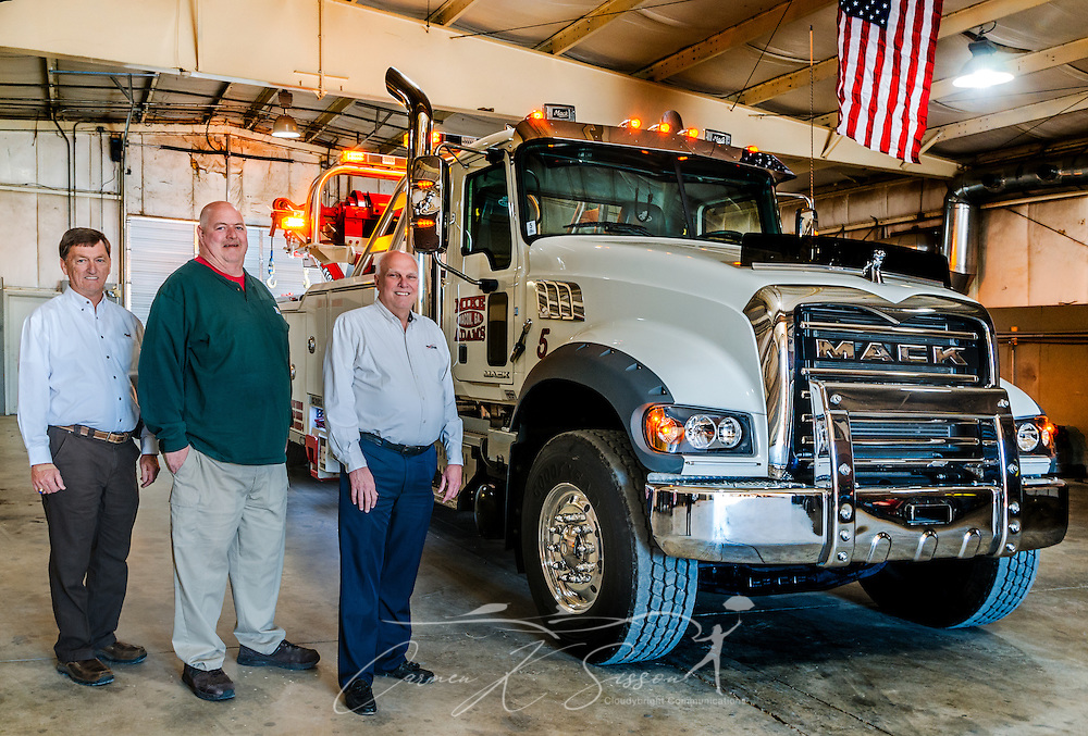 Mike Adams (centered) stands beside Tommy Bush, left, account manager at Nextran Truck Centers, and David Bennett, right, general manager at Nextran, March 22, 2016, at Mike Adams Towing and Air Cushion Recovery in Macon, Georgia. Adams purchased most of his fleet from Nextran, including his most recent acquisition, a 2016 Mack Granite with a 50-ton Century rotator. (Photo by Carmen K. Sisson/Cloudybright)