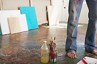 Artist standing by paint brushes and paint thinner in studio low section