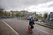 Een vrouw loopt over de Keizersgracht in Amsterdam.<br /> <br /> A woman is walking at the Keizersgracht in Amsterdam.