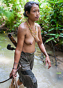 Mentawai indigenous woman fishing with net in river (Indonesia).