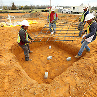 Workers with Gene Waters Concrete of Guntown, a subcontractor with Century Construction, place rebar in the footings on the construction site of the Fairpark Towers in Tupelo on Tuesday morning.