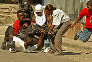 Port-Au-Prince--  March 7, 2004         During  a rally to celebrate the departure of deposed president Jean Bertran Aristide (pls cq this for me) in Port-Au-Prince a Haitian police officer who was shot in the foot  is carried out of a firefight after pro-Arisitde forces attacked the demonstrators. photo  by essdras m suarez/globe staff