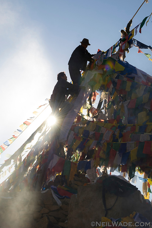 Two Tibetan men hang prayer flags near the Namgyal Tsemo Gompa in Leh, India.