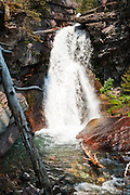 Baring Falls tumbles onto red rocks, a short walk downstream from Sunrift Gorge along the Going-to-the Sun Road in Glacier National Park, Montana, USA. Since 1932, Canada and USA have shared Waterton-Glacier International Peace Park, which UNESCO declared a World Heritage Site (1995) containing two Biosphere Reserves (1976). Rocks in the park are primarily sedimentary layers deposited in shallow seas over 1.6 billion to 800 million years ago. During the tectonic formation of the Rocky Mountains 170 million years ago, the Lewis Overthrust displaced these old rocks over newer Cretaceous age rocks.