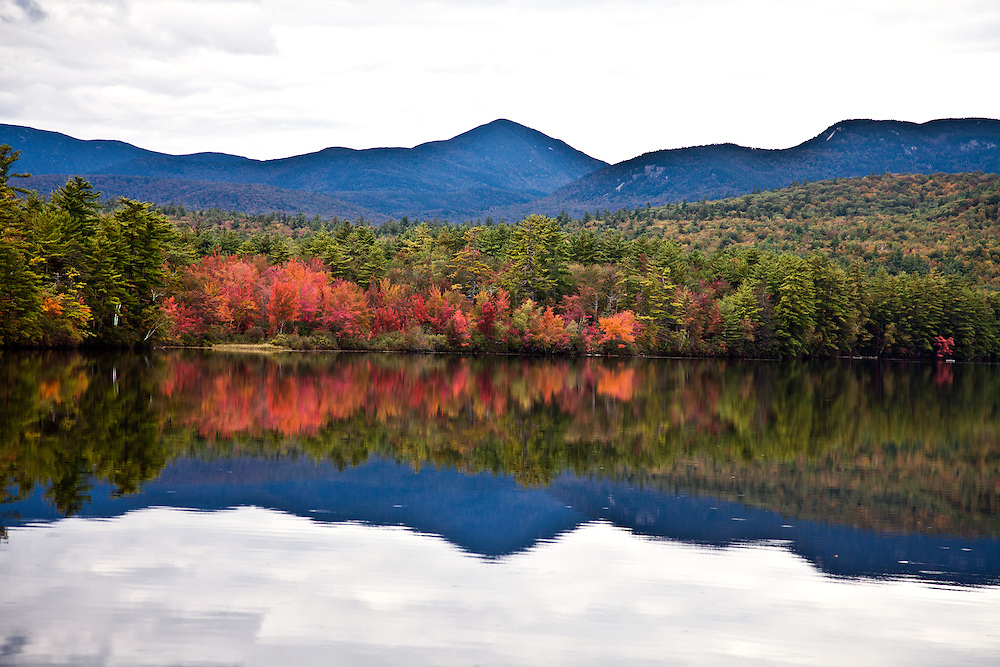 Fall color -- sugar maples -- blaze as a reflection in an unnamed lake, off Highway 113, south of Conway.