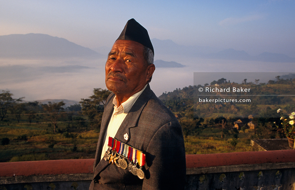 "The rare Victoria Cross is worn on the chest of the celebrated Nepali war veteran Bhanu Bhagta Gurung (also written Bhanubhakta), an ex-soldier of the British Gurkha regiment who in the second world war, earned his medals from repeated bravery against Japanese positions in Burma. He sits here on the terrace of his home, above the misty valley of Gorkha, Central Nepal. He is one of the last survivors of the remarkably brave men  who helped defeat the enemy in the jungles of south-east Asia. Gurung is the name of his Nepalese tribe (like the Sherpas who also come from the high Himalayan Kingdom). His company commander described him as ""a smiling, hard-swearing and indomitable soldier who in a battalion of brave men was one of the bravest"". Born September 1921 - died March 1 2008."