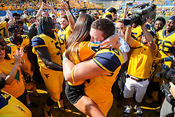 Oct 6, 2018; Morgantown, WV, USA; West Virginia Mountaineers defensive lineman Reese Donahue (46) proposes to his fiancée at midfield after beating the Kansas Jayhawks at Mountaineer Field at Milan Puskar Stadium. Mandatory Credit: Ben Queen-USA TODAY Sports