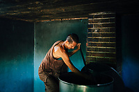 A monk stirs a vat of elixir at Tham Krabok temple. The recipe is known to only a handful of monks at the temple, and is passed down through an apprentice program.