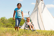 Indian girl and brother, Crow Indian Reservation, Montana, tipi
