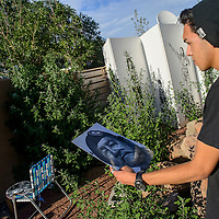 072314  Adron Gardner/Independent<br /> <br /> Artist Greg Ballenger compares a photographic portrait of his uncle Eugene Attcity to the mural he is painting on the stucco wall of Fitz Sergent's home in Gallup Wednesday.