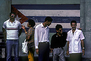 Habaneros waiting for a bus in front of a mural depicting the national flag. 1992