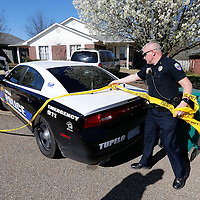 Thomas Wells | BUY at PHOTOS.DJOURNAL.COM<br /> Tupelo Police officer Tim Bell begins to take down the crime scene tape around a home on Crestview Road following a shooting that eneded with a suspect being charged with murder.