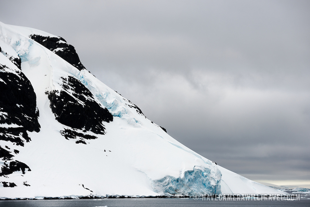 "Scenic mountains covered in snow and ice lining the side of the Lemaire Channel on the western side of the Antarctic Peninsula. The Lemaire Channel is sometimes referred to as ""Kodak Gap"" in a nod to its famously scenic views."