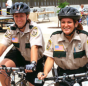 Two happy park ranger policeladies age 28 patrolling Mississippi River Carp Festival.  Brooklyn Park Minnesota USA