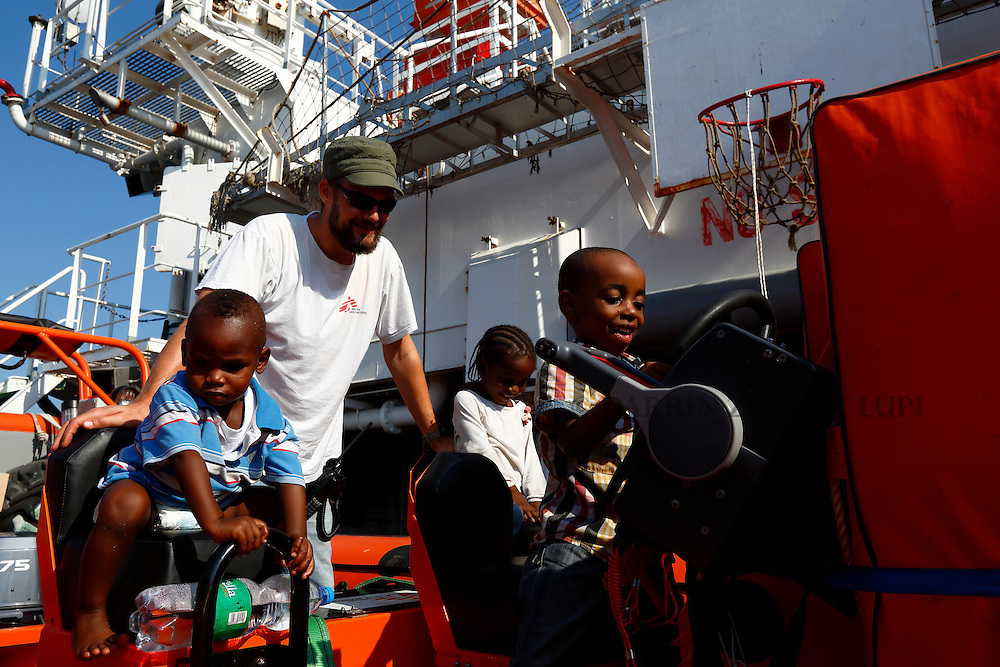 Migrant children play on a rigid hulled inflatable boat (RHIB) under the watchful eye of an Medecins san Frontiere (MSF) team member on board the MSF rescue ship Bourbon Argos somewhere between Libya and Sicily August 8, 2015.  Some 241 mostly West African migrants on the ship are expected to arrive on the Italian island of Sicily on Sunday morning, according to MSF.<br /> REUTERS/Darrin Zammit Lupi <br /> MALTA OUT. NO COMMERCIAL OR EDITORIAL SALES IN MALTA