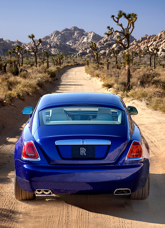 2015 Rolls Royce Wraith, Salamanca Blue.  Photographed in Joshua Tree, CA. rear view on a dirt road.